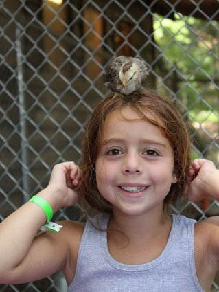 Young girl with small bird on head