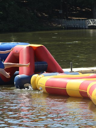Girl jumping from inflatable obstacle course on lake