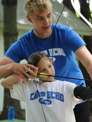 Camp echo instructor helping girl with bow & arrow