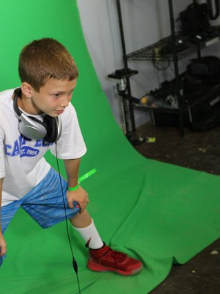 Young boy being filmed in front of a green screen