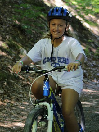 Girl riding mountain bike through a wooded trail