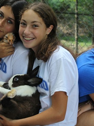 Girls holding small hamster and black and white rabbit