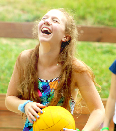 girl holding yellow volleyball laughing