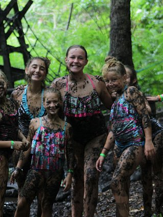 Group of girls covered in mud hiking on a wooded path